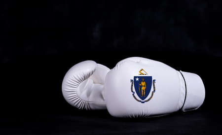 Boxing glove with Massachusetts flag on black background.