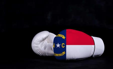 Boxing glove with North Carolina flag on black background. Фото со стока