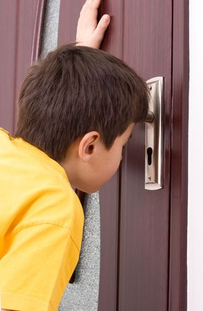 peeking: Boy looking through keyhole
