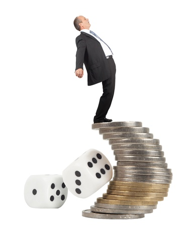 Unbalanced business man on a top of coins pile -concept of business risk photo