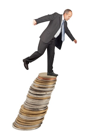 imbalance: Unbalanced business man on a top of coins pile -concept of business uncertainty Stock Photo