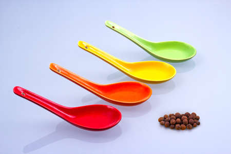 sundry: Colorful spoons with allspice  isolated on white background Stock Photo