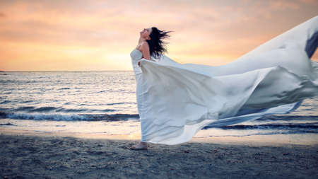 Beautiful young woman in white dress on a stormy beach