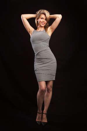Portrait of a happy beautiful woman in a gray dress