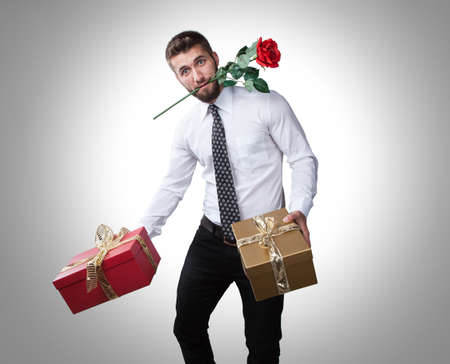 Attractive man with presents in his hands and a rose in his mouth 免版税图像