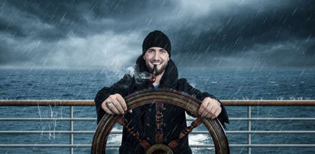 Attractive man with beard is driving the ship through rough seas Stockfoto