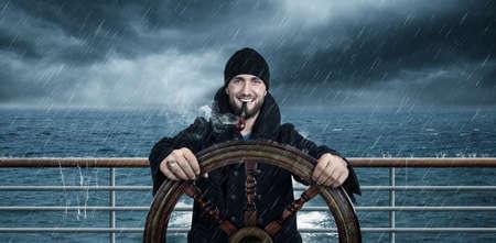 Attractive man with beard is driving the ship through rough seas Archivio Fotografico