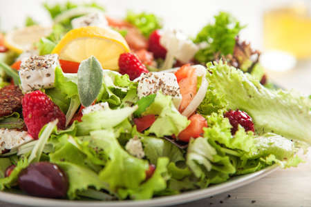Summer salad with green lettuce and a lemon