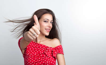 Beautiful happy woman is showing her thumb up