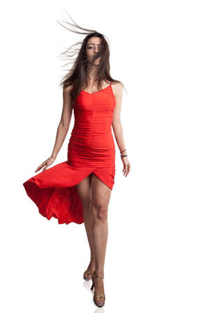 Beautiful woman in a red dress and wind in her hair is walking through the camera