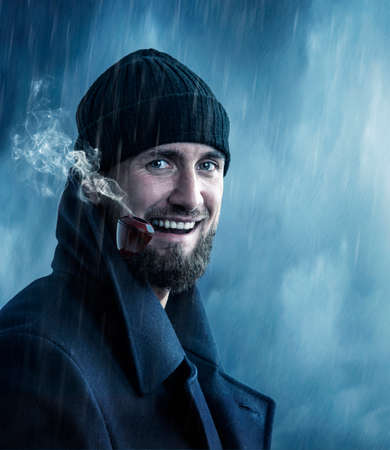 Attractive man smoking a pipe in the rain
