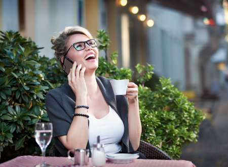 Beautiful blond woman is sitting in a coffee shop and holding a smart phone in her hand