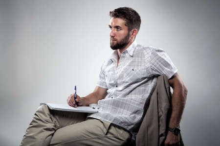 Attractive man is writing on paper