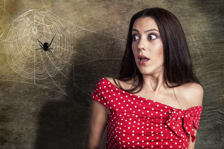 Beautiful woman is shocked to a spider next to her face