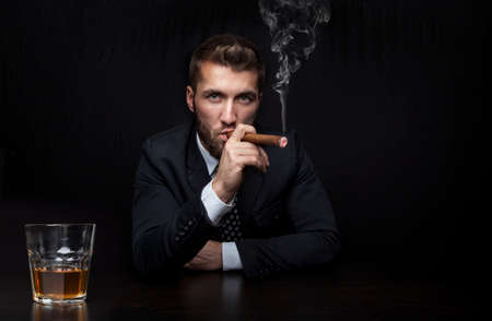 Attractive business man with a cigar and a drink