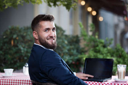 Attractive man with a laptop makes a break in a restaurant