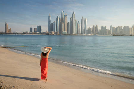 Beautiful woman with a red dress is walking on the beach in Dubai. In the background there is the skyline from Dubai Marina