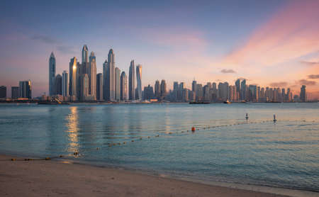 Skyline of Dubai Marina at sunset with a beautiful beach in the foreground