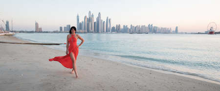 Beautiful woman with a red dress is walking on the beach in Dubai. In the background there is the skyline from Dubai Marina Archivio Fotografico - 98484085