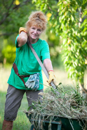 Attractive pensioner is working in her own garden