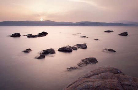 Scattered rocks in the sea at sunset Banque d'images