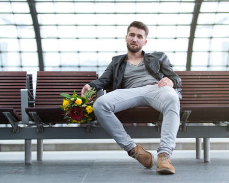 Attractive man with flowers in his hand is waiting at a train station Banque d'images