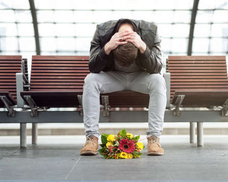 Sad man is sitting alone at the train station with his head down Stockfoto