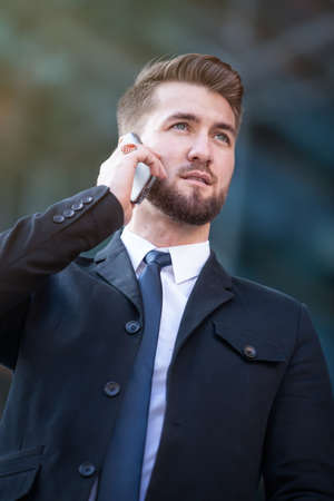 Attractive business man walks through berlin while talking on his smart phone