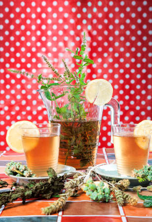 Homemade ice tea with lemon on a red background
