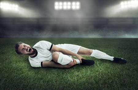Attractive soccer player is lying on the floor and screaming and holding his leg Stock fotó