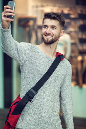 Attractive man with a beard is taking a photo of himself Stock fotó