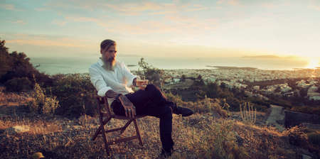 Attractive bearded businessman is sitting on the chair and drinking whiskey at sunset