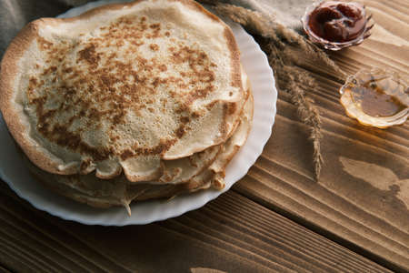 Close up shot Home made pancakes with honey and strawberry jam on a wooden table