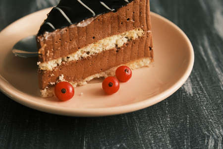 Piece of chocolate cake on a plate on a dark table