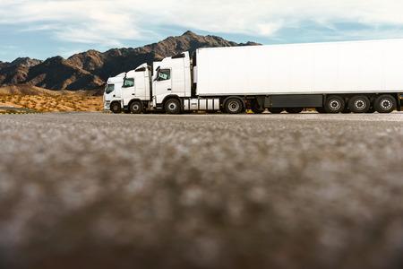 transporte: Três caminhões brancos em um estacionamento de uma empresa de transporte esperando a próxima ordem. Tiro de baixo ângulo, espaço da cópia na parte inferior da imagem