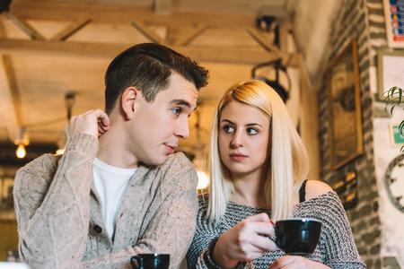 어떤 결정을 내릴 카페에서 두 젊은 성인. 자연의 빛, 필드의 좁은 깊이. 스톡 콘텐츠