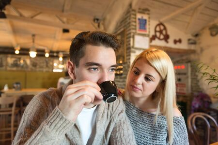 two person only: Two young adults (couple) in a cafe. Focus on the closer person, narrow depth of field with only the enviromental and natural light.