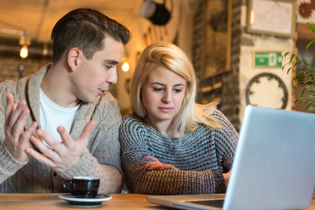 decision making: Young couple sitting in the cafe with laptop making some important decisions. The foreground is blurred, narrow depth of field, natural and enviromental light. Stock Photo