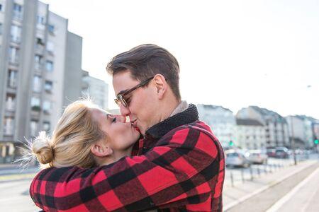 novios besandose: Joven elegante kissng pareja bonita y divertirse al aire libre en una cita. Fondo borroso Foto de archivo