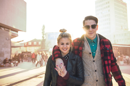 enhanced: Happy stylish hipster couple walking on the streets. Warm tones, a little bit enhanced on the background. Lens falre added to enhace the sunlight effect