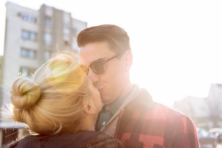 personas besandose: Retrato al aire libre de la pareja de Sunny estilo joven bes�ndose en la calle. Los tonos c�lidos, a�aden reflejo en la lente para mejorar el estado de �nimo.