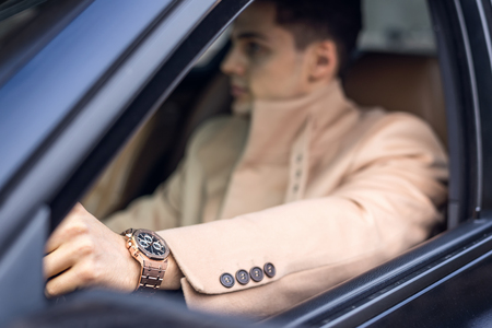 watch movement: Handsome stylish male driving the car, focus on the watch (foreground). Natural light Stock Photo