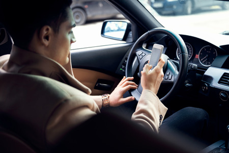 Stylish young man using mobile phone ih the car. Archivio Fotografico