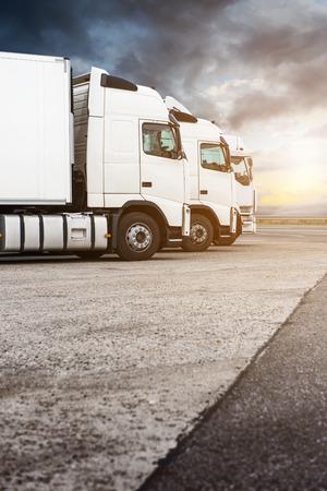 Drie witte vrachtwagens op een rij te wachten voor de volgende bestelling. Dramatische hemel toegevoegd lens flare en warme tinten. Kopieer de ruimte aan de onderkant van het frame.
