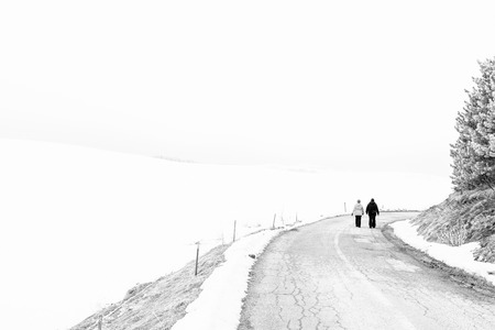 lonliness: Two people waliking alone on the road. Black and white photo, copy space on the left side of the frame.