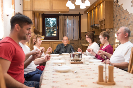 Big generation family having dinner together and holding each other by hands while praying. Focus in the center of the frame on the grandpa, natural light used. Horizontal composition, narrow depth of field