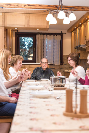 Big generation family having dinner together and holding each other by hands while praying. Focus in the center of the frame on the grandpa, natural light used. Vertical composition, narrow depth of field photo