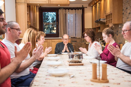 family praying: Generaci�n de la familia grande de cenar, rezando. Enfoque en el centro del cuadro en el abuelo, luz natural utilizado. Composici�n horizontal, profundidad de la luz natural fieldm Foto de archivo