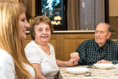 Mature couple having great time with their family, romantic emotional moments, the grandma is looking at the camera and smiling. Blurred foreground, shallow depth of field. photo