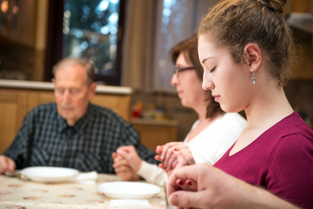 prayers: Big generation family having dinner together and holding each other by hands while praying. Focus on the young girl, natural light used. Horizontal composition; shallow depth of field